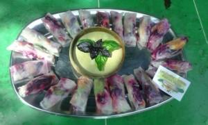 Herfstgroentenrol van maisfilodeeg gevuld met wortel, komkommer, groene kool, rode biet, veldsla, snijbiet en avocado geserveerd met een basilicum-rucola-tahinpesto.